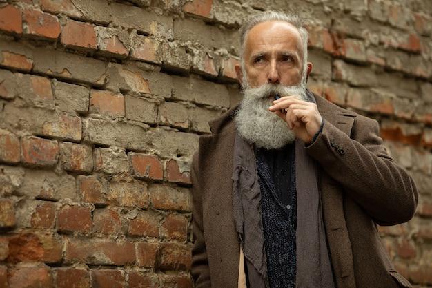 Cavalheiro elegante com barba longa fumar ao ar livre.