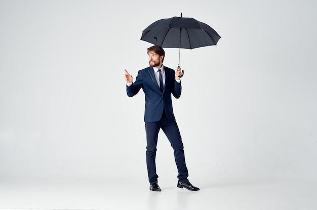 Cavalheiro elegante com guarda-chuva escuro sobre fundo claro e terno clássico