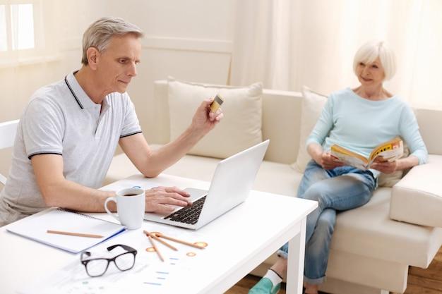 Cavalheiro inteligente e focado que emprega tecnologias modernas para administrar seu dinheiro e fazer pagamentos em casa