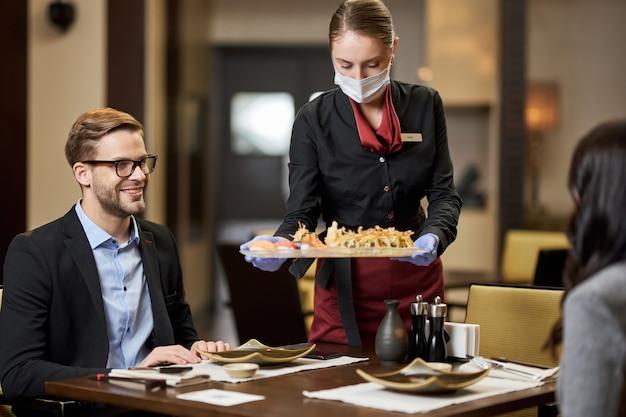 Cavalheiro satisfeito e sua acompanhante servindo sushi em restaurante