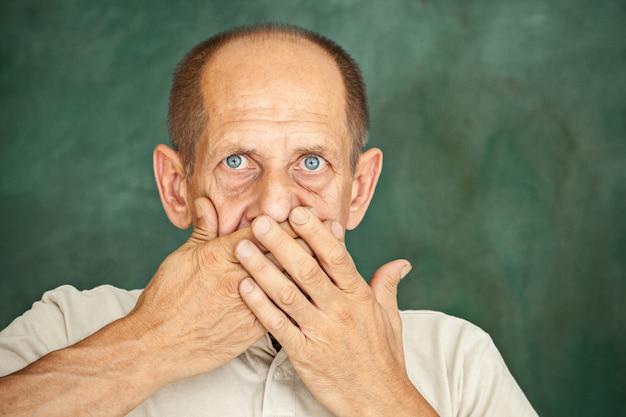 Cavalheiro sênior chocado, segurando a mão contra a boca e olhando para a câmera