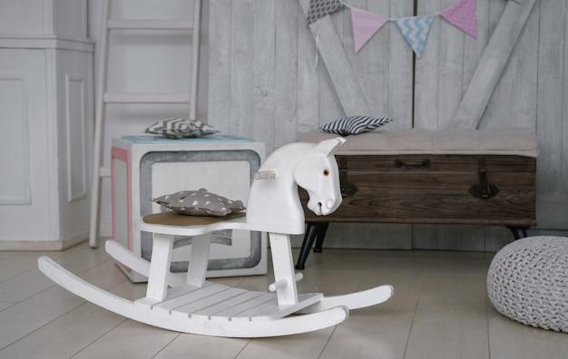Cavalo de balanço de madeira branco no quarto de crianças a brincar