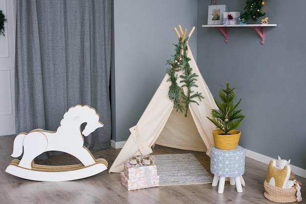 Cavalo de balanço em uma sala de crianças decorada para o natal