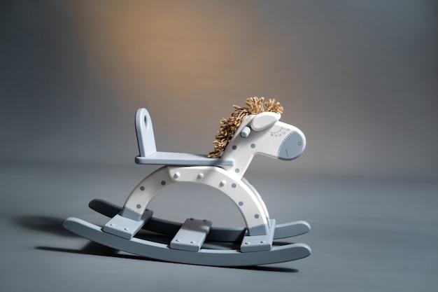 Cavalo de balanço feito à mão sobre um fundo cinza.