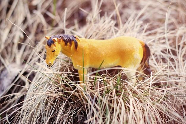Cavalo de brinquedo na natureza fotografado como real entre a grama seca como palheiros