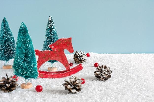 Cavalo de brinquedo retrô de natal com pinheiros, bagas vermelhas e pinhas na mesa de madeira coberta de neve