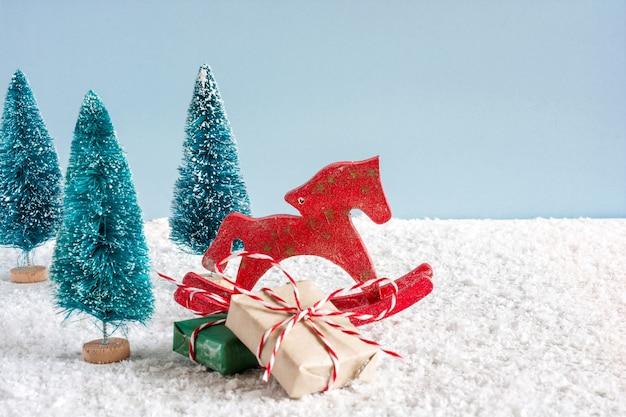 Cavalo de brinquedo retrô de natal com pinheiros e caixas de presente na mesa de madeira coberta de neve