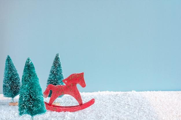 Cavalo de brinquedo retrô de natal com pinheiros na mesa de madeira coberta de neve