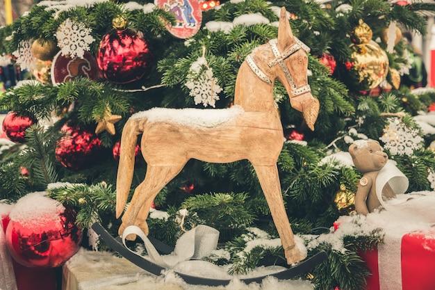 Cavalo de brinquedos de natal e neve na árvore de natal do ramo