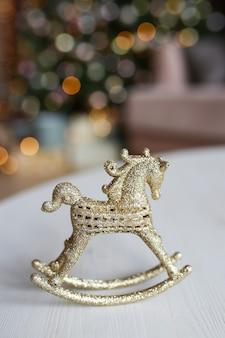 Cavalo de decoração de brinquedo dourado em pé sobre a mesa, no contexto de um bokeh de árvore e guirlandas
