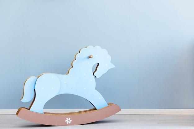 Cavalo de papelão azul, brinquedo de crianças balançando, parede azul interior