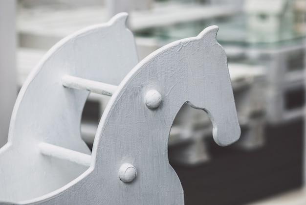 Cavalo de pau velho de madeira contra um playground