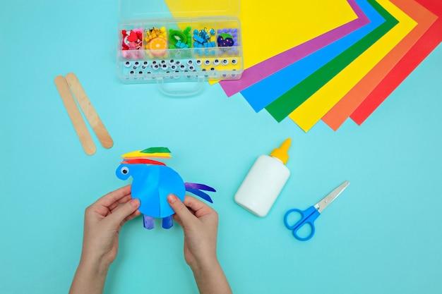 Cavalo feito de papel sobre uma mesa azul, as mãos das crianças fazem artesanato da cor mágica do cavalo