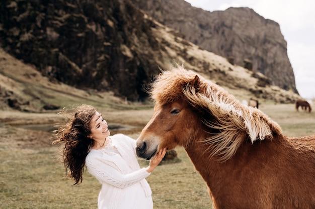 Cavalo islandês e mulher em um vestido branco