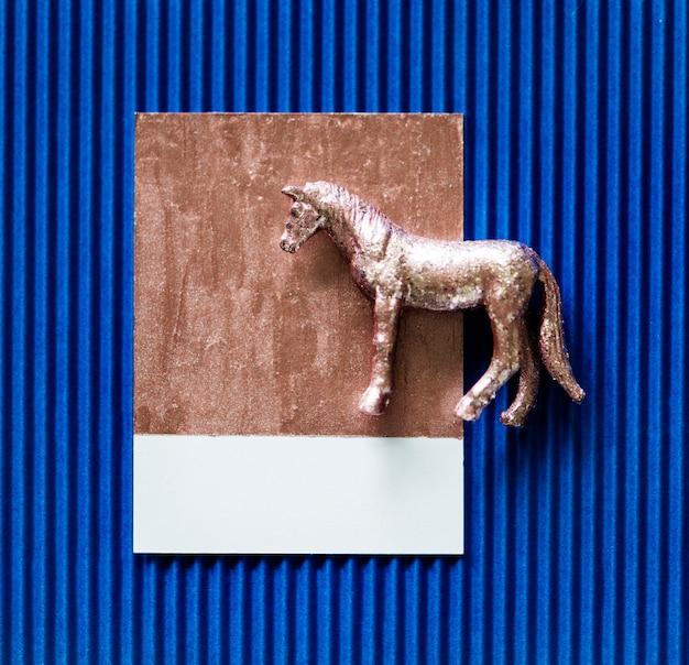 Cavalo metálico minúsculo em papel azul