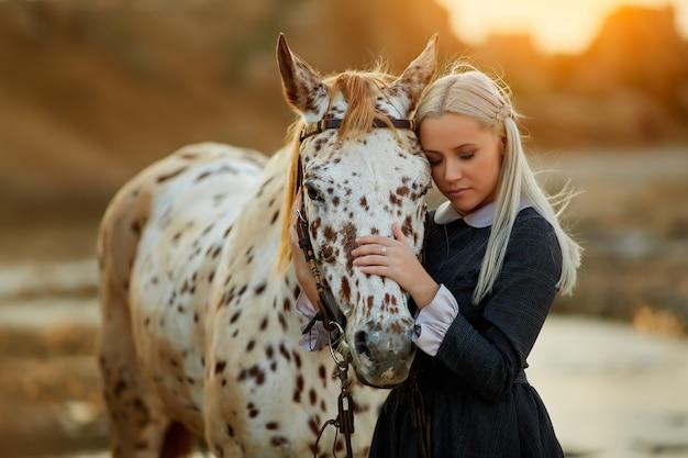 Cavalo sensual, abraçando a mulher na luz solar