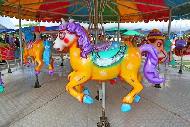 Cavalos em um carnaval merry go round na feira do templo