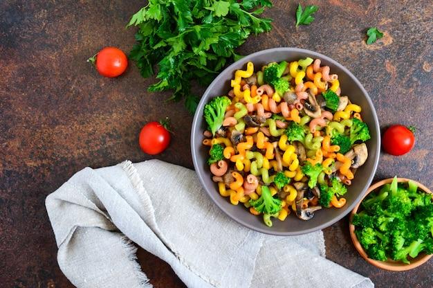 Cavatappi colorido macarrão com brócolis e cogumelos. macarrão colorido. macarrão com legumes. a vista de cima