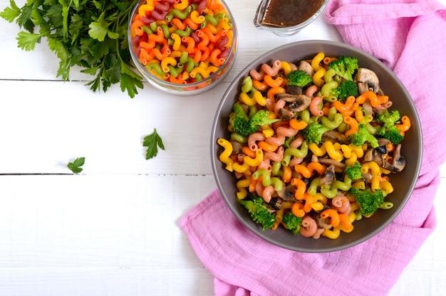 Cavatappi coloriu a massa com brócolis e cogumelos em uma superfície de madeira branca. macarrão colorido. macarrão com legumes. a vista de cima