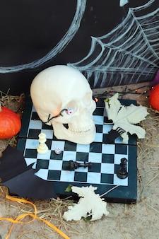 Caveira de decoração de halloween em um tabuleiro de xadrez, folhas de outono e iluminações de fundo preto