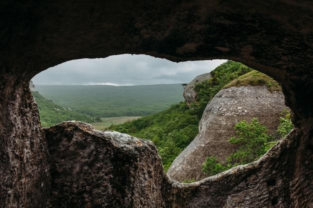 Caverna antiga e vale da floresta de montanha verde