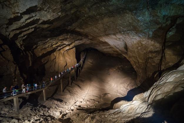 Caverna de athos nova, abkhazia. as pessoas andam ao longo da ponte dentro da caverna