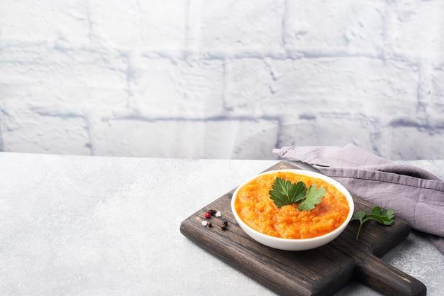 Caviar caseiro de abobrinha, tomate e cebola em um prato de cerâmica, sobre uma superfície cinza. conservas de produção caseira, legumes cozidos em conserva. copie o espaço