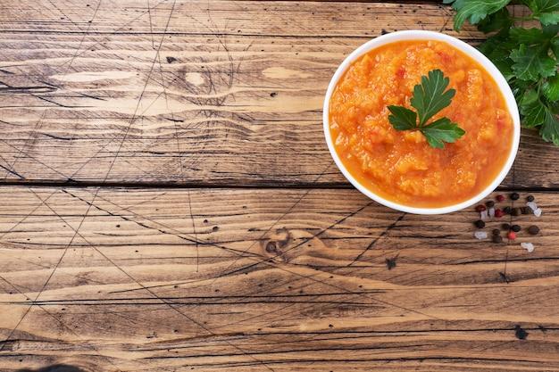Caviar caseiro de abobrinha, tomate e cebola em uma placa de cerâmica em um fundo de madeira. conservas de produção caseira, legumes cozidos em conserva.