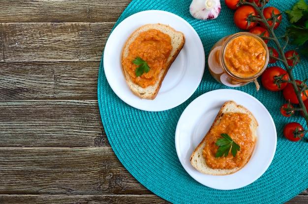 Caviar de abóbora deliciosa em uma jarra e espalhe sobre fatias de pão branco em cima da mesa. caviar caseiro com abobrinha, alho, cenoura, molho de tomate. cozinha vegana. a vista de cima configuração plana