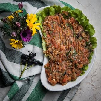 Caviar de berinjela com alface, manjericão em um prato branco com toalha de mesa
