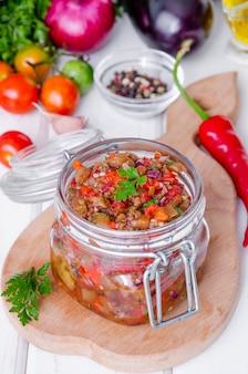 Caviar de berinjela com tomate e pimentão assado em uma jarra de vidro