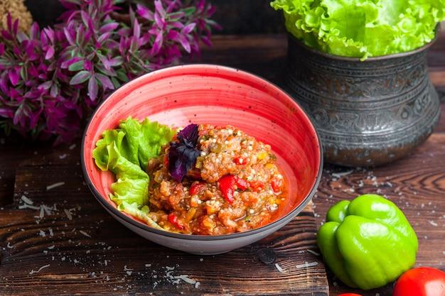 Caviar de berinjela de vista lateral caviar de berinjela com salada de manjericão e tomate deixa em uma mesa de madeira escura horizontal