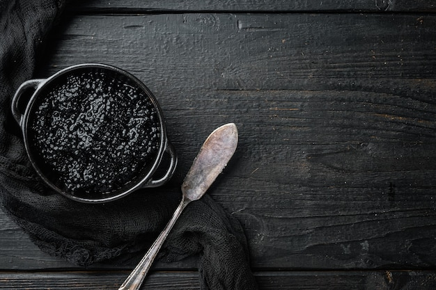 Caviar de esturjão preto em uma tigela na mesa de madeira preta