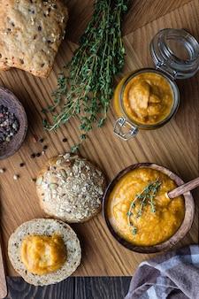 Caviar de legumes delicioso em uma tigela de madeira e jarro servido com pão multigrain.