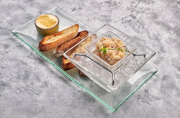 Caviar de lúcio, no gelo, com croutons e manteiga, em um prato transparente, sobre um fundo branco