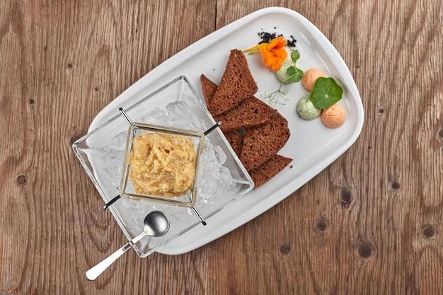 Caviar de pique em um prato branco com torradas e gelo
