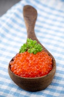 Caviar de salmão com colher na mesa cinza.