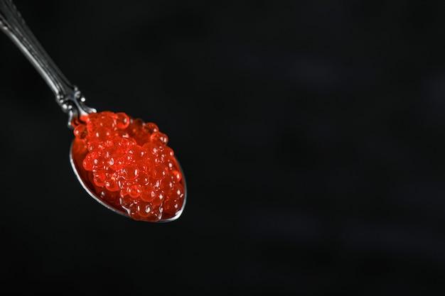 Caviar de salmão vermelho em uma colher metálica