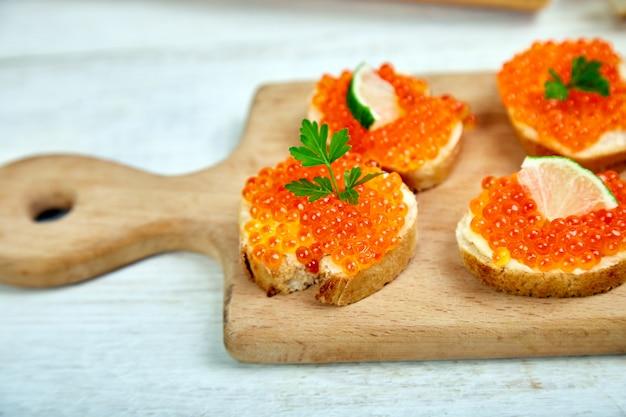 Caviar de salmão vermelho na tigela e sanduíches com tábua de madeira