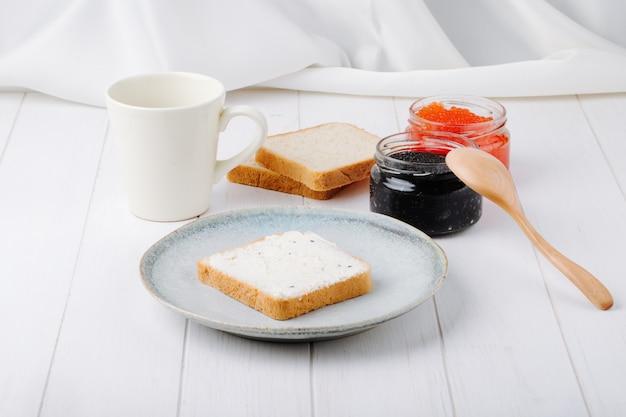Caviar de vista frontal preto e vermelho com torradas com manteiga em um prato com uma xícara de café