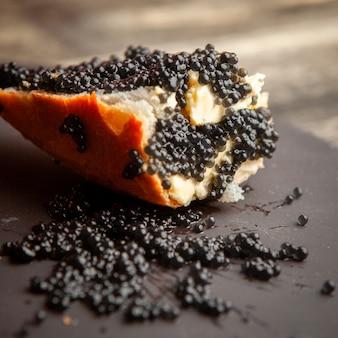 Caviar preto da vista lateral no pão e no fundo escuro.