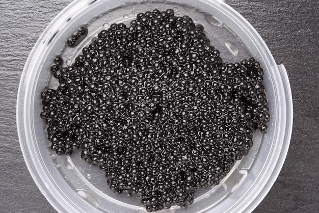 Caviar preto de paddlefish em prato de plástico, comida gourmet e deliciosa, close