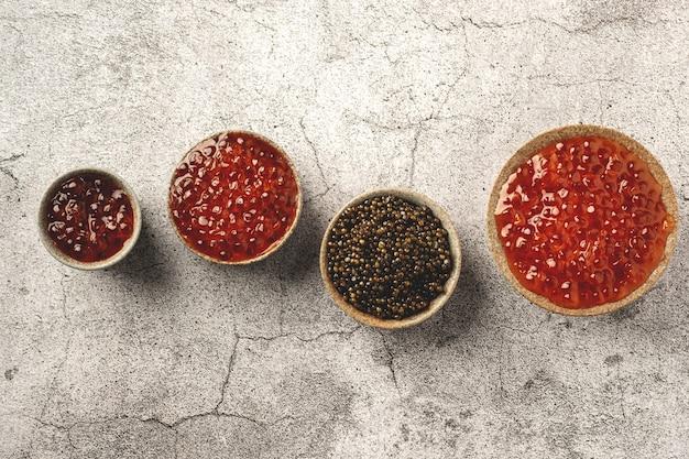 Caviar preto e vermelho em taças sobre uma mesa de concreto cinza, cópia espaço, vista superior
