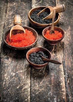 Caviar preto e vermelho em tigelas de madeira velhas na mesa de madeira.