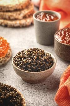 Caviar preto e vermelho em tigelas, lanches em uma mesa de concreto cinza