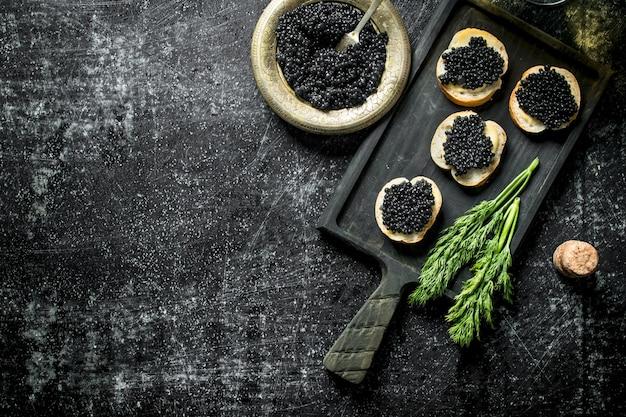 Caviar preto em fatias de pão com endro. na mesa rústica preta