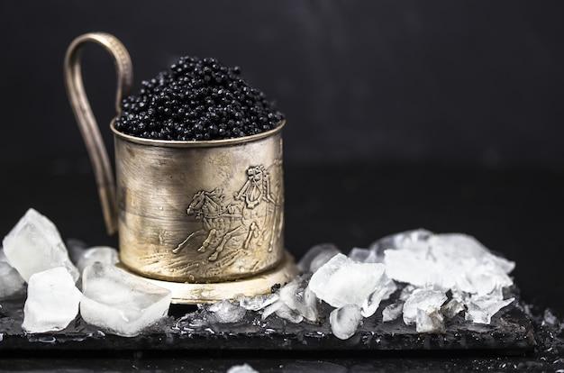 Caviar preto em uma tigela. close-up de caviar preto de esturjão natural real de alta qualidade. delicatessen. textura de caviar de luxo caro prato quadrado em preto