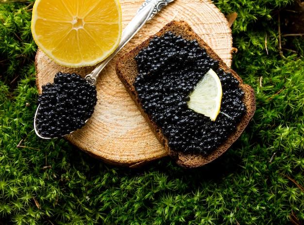 Caviar preto em uma tigela de prata com gelo e uma colher de prata sobre fundo de darck. caviar preto prateado. caviar preto