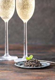 Caviar preto no prato com duas taças de champanhe