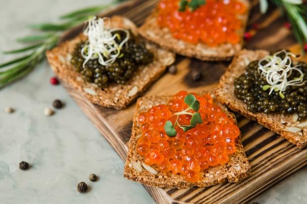 Caviar vermelho caro chique, caviar de pique e caviar preto para um lanche